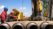 stock photo of crude-oil  - Oil drilling rig workers lifting drill pipe - JPG
