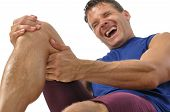 stock photo of clutch  - Male athlete on floor clutching knee and hamstring in excruciating pain on white background - JPG