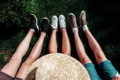 Image Of Several Legs On Green Grass Wearing Sneakers.a Part Of Straw Hat On The Image. poster