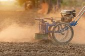 Thai Farmer Working In The Land And Making The Hole On Soil With Machine To Prepare The Soil For Gro poster