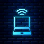 Glowing Neon Laptop And Free Wi-fi Wireless Connection Icon Isolated On Brick Wall Background. Wirel poster