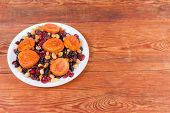 White Dish With Dried Apricots, Different Raisins, Other Dried Fruits And Berries Located Left On Th poster