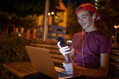 Portrait of a smiling young man with a smartphone, in the street.  Happy teenage boy is using mobile poster