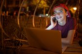 Portrait of a smiling young man with a smartphone, in the street at night.  Happy teenage boy is cal poster