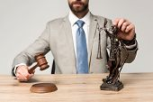 Partial View Of Judge Holding Gavel And Themis Statue Isolated On Grey poster