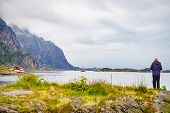 Sea Landscape With Male Tourist On Shore, Lofoten Islands, Henningsvaer Region, Norway. Hazy Day, Ov poster