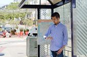 stock photo of bus-shelter  - A young Asian man at a bus stop checking his watch as he waits