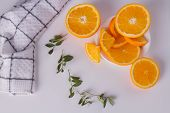 Sliced Orange Fruit And Green Leaves. Tasty Orange Fruit Slices On White Background. poster