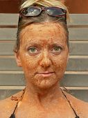 image of mud pack  - woman relaxes as she gets a pampering facial - JPG