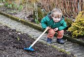 picture of hoe  - Little boy in spring with garden hoe outdoors - JPG