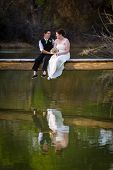 picture of dock a pond  - Affectionate lesbian couple sitting on dock above lake - JPG