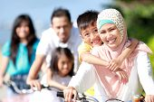 stock photo of muslim man  - Happy asian family riding bikes in the beautiful morning outdoor - JPG
