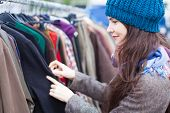 foto of flea  - Attractive woman choosing clothes at flea market - JPG