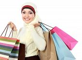 stock photo of muslimah  - Happy young muslim woman with shopping bag isolated over white background - JPG