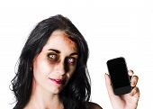 foto of gruesome  - Bruised and bloody zombie woman holding a mobile phone - JPG