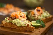 stock photo of shrimp  - Wholegrain toast bread slices with guacamole fried shrimp and fried bacon pieces on wooden board  - JPG