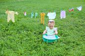 picture of wash-basin  - The little girl in a small basin with foam near the rope with wash clothes - JPG