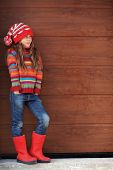 Cute little girl wearing knit winter clothes posing over wooden background