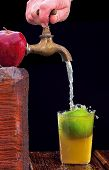 stock photo of cider apples  - Apple with faucet and natural cider on black background - JPG