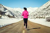 stock photo of snowy-road  - Woman running in cross country road on winter. Rear view of female runner training for marathon in snowy mountains landscape. ** Note: Shallow depth of field - JPG