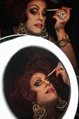 picture of drag-queen  - Drag queen applying makeup in front of a mirror - JPG