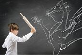 stock photo of tyrannosaurus  - Concept of courage with brave boy fighting a dragon - JPG