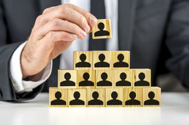 stock photo of human pyramid  - Closeup of manager hand arranging wooden cubes wit person shape in a pyramid - JPG