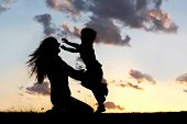 foto of candid  - a silhouette of a happy young boy child running into the arms of his loving mother for a hug in front of the sunset in the sky - JPG
