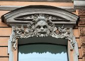 stock photo of building relief  - Fragment an ancient building with window decorated with bas - JPG