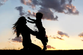 foto of boys night out  - a silhouette of a happy young boy child running into the arms of his loving mother for a hug in front of the sunset in the sky - JPG