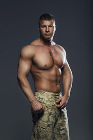 foto of hunk  - Muscular young sexy soldier man in green wear - JPG