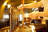 stock photo of tapping  - cold beer in the hand and beer taps - JPG