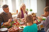 picture of happy thanksgiving  - Happy family of four eating traditional Thanksgiving food by the table - JPG