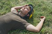 stock photo of young men  - Young cyclist lying on a ground with eyes closed - JPG