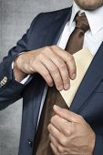 image of tribute  - Business man Hiding Bribes - JPG