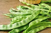 image of bean-pod  - a pile of green bean pods on a wooden table - JPG