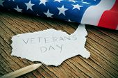 stock photo of veterans  - a piece of paper in the shape of United States with the word Veterans Day on a wooden background with the flag of the United States in the background - JPG