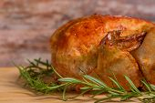 picture of roast chicken  - a roasted chicken with rosemary on a wooden background - JPG