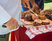 stock photo of buffet  - Chef carving meat on a buffet table carving station - JPG