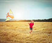 stock photo of sun flare  - happy little girl witha kite in a field - JPG