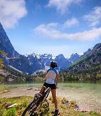 foto of beside  - Young woman riding bike beside a lake in  Alps - JPG