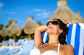 picture of mayan  - Joyful woman at tropical resort caribbean beach resting on outdoor chaise lounge - JPG