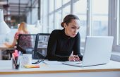 picture of woman  - Image of woman using laptop while sitting at her desk - JPG