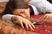 stock photo of fatigue  - Close up portrait of a business woman tired and sleeping in an hotel bed with a mobile phone - JPG