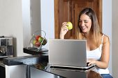 pic of entrepreneur  - Entrepreneur woman browsing a laptop and eating at home in the kitchen - JPG