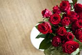stock photo of bunch roses  - Bunch of red roses on a wooden floor - JPG
