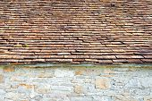 foto of red roof tile  - Part of red clay tiled roof and natural stone wall - JPG