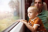 picture of lap  - Father with son in his lap traveling in train - JPG