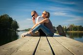 stock photo of she-male  - couple relaxing on a pier she is hugging him while he is speaking on the phone - JPG