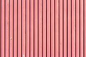 foto of red siding  - Peeling red paint on a corrugated metal surface - JPG